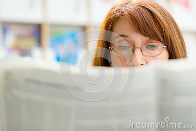 Elderly woman reading newspaper in library