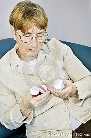 Free Elderly Woman Reading Pill Bottles Royalty Free Stock Photography - 8467387