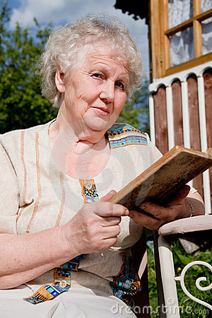 Elderly woman reads a book