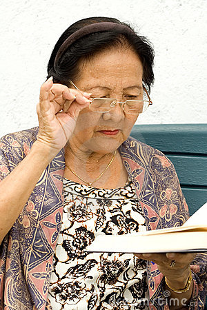 Elderly woman in serious reading