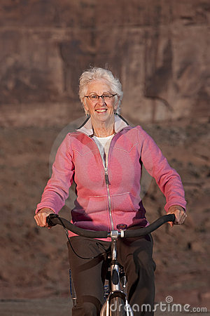 Free Elderly Woman Smiling On A Bike Royalty Free Stock Image - 13713846