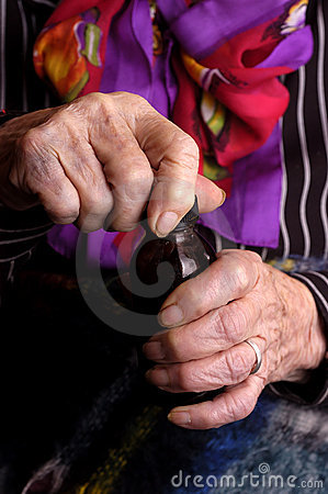 Elderly women opening medication bottle