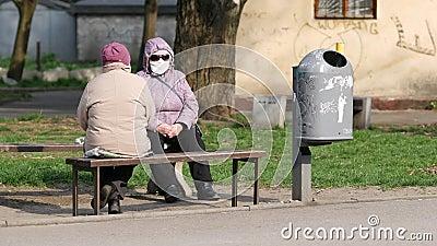 Elderly women sitting on street bench wear face masks and  talks. Quarantine stock video