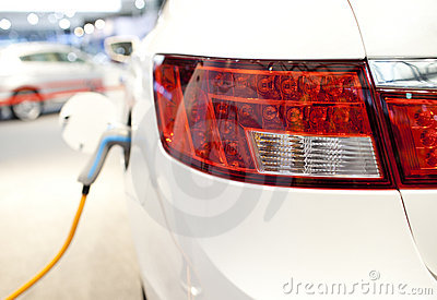 An electric car in charge with green cable