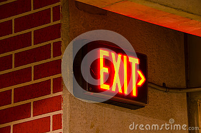 Electric exit sign on brick concrete wall at night