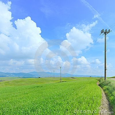 Electric power line, green field and blue sky