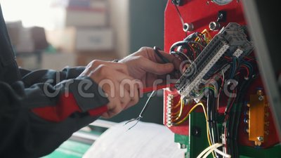 Electrician`s hands installing energy system on machinery industry. Close up stock footage