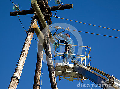 Electrician working on power line pole