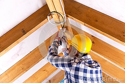 Electrician working with wires at attic renovation site Stock Photo