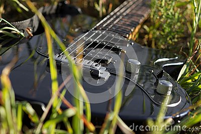 Electro guitar lying in grass