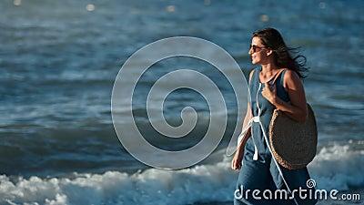 Elegance feliz viajando senhora relaxa ao ar livre indo na costa contemplando a paisagem hídrica no nascer do sol vídeos de arquivo