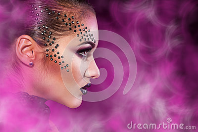Elegance female in studio with multicolored smoke