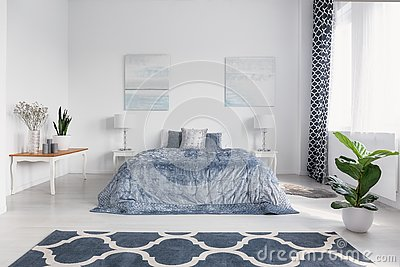 Elegant bedroom interior with big comfortable bed with blue bedding, paintings on the wall and patterned carpet on the floor, real Stock Photo