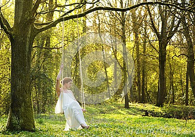 Elegant bride in white wedding dress sitting alone on swing outdoors