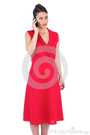 Elegant brunette in red dress on the phone posing