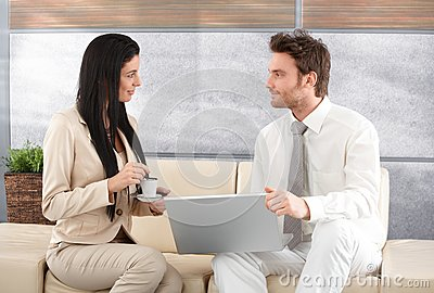 Elegant businesspeople using laptop talking