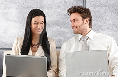 Elegant couple sitting on sofa using laptop Stock Photo