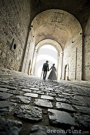 An elegant couple walk in the tunnel