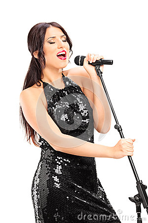 Elegant female singer singing on microphone