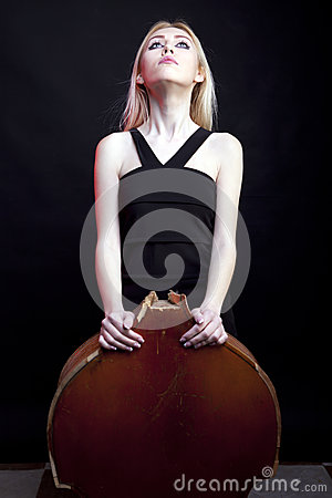 Elegant girl behind a broken contrabass on black background