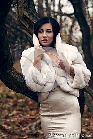 Elegant girl in white coat with high collar