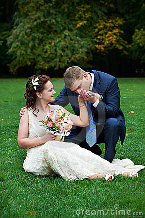 Elegant groom kisses hand of his beautiful bride