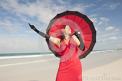 Elegant happy woman red dress beach