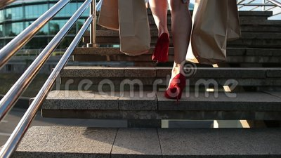 Elegant legs of woman with shopping bags on stairs stock video