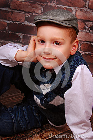 Elegant little boy in a cap and wool vest