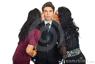 Elegant man being kissed by two women