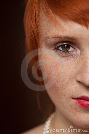 Elegant redhead with freckles on brown background