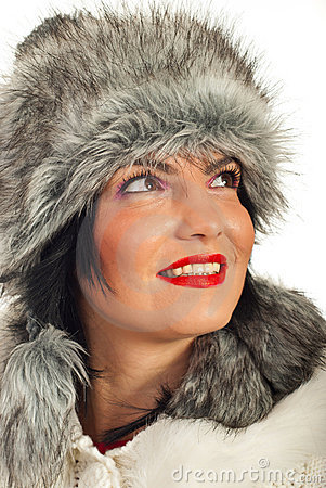 Elegant woman in fur hat looking up
