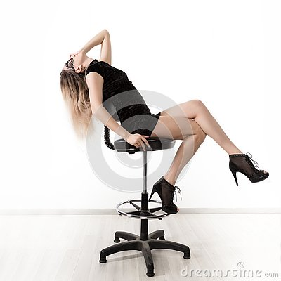 Free Elegant Womanin A Little Black Dress Is Posing While Sitting On A High Chair And Spreading Her Legs. Girl On A Royalty Free Stock Photos - 139973078