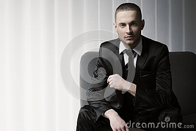 Elegant young fashion man in tuxedo on a sofa, blinds background