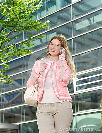 Elegant young lady talking on mobile phone outdoors