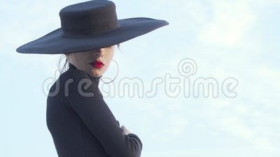 Elegante mujer labradora roja vestida de negro girando hacia la cámara almacen de video