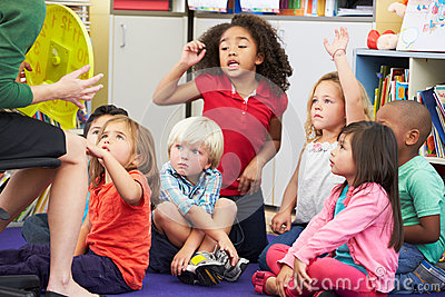 Elementary Pupils In Classroom Learning To Tell The Time