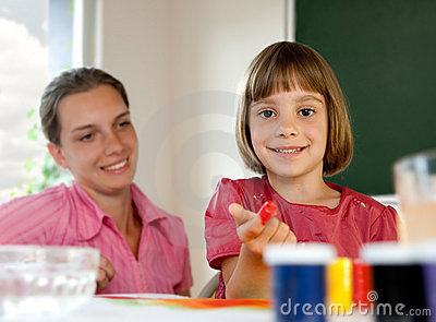 Elementary school pupil painting with teacher