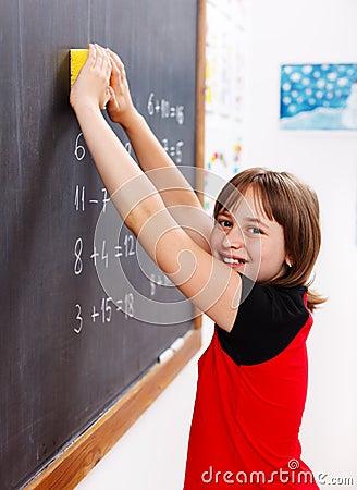 Elementary school student erasing chalkboard