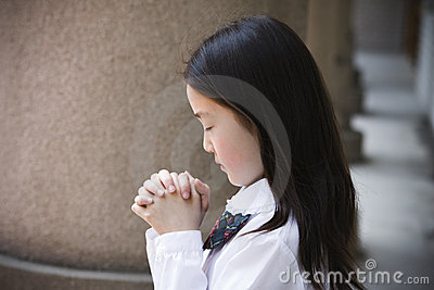 Elementary schoolgirl praying