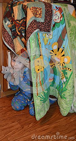 Sweet and happy toddler in pajamas, and his elephant, peeks out from under the blankets of his fort.