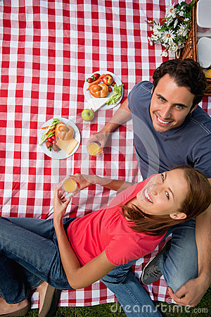 Elevated view of two smiling friends as they lie on a blanket wi