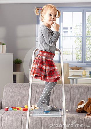 Elfish little girl on top of ladder at home