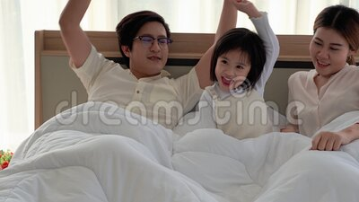 Eltern ziehen ihre Töchter auf ein Bett in einem Haus voller Glück und Komfort stock footage