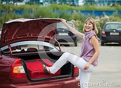 Embalaje de la mujer su bagaje en el coche