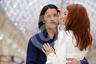 Embracing couple - dark-haired man and red-haired woman