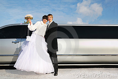 Embracing groom and bride stand near limousine