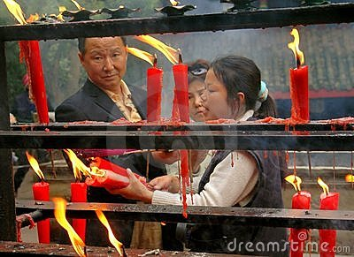 Emeishan, China: Lighting Candles at Temple Editorial Image
