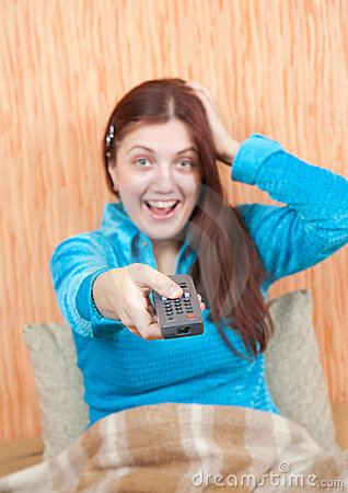 Emotional girl changing channels with clicker