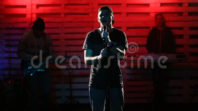 Emotional singer singing on illuminated stage stock video